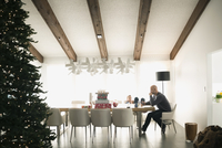 Man sitting at dining table near Christmas tree