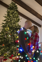 Couple wrapped in Christmas string lights kissing