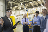 Manager with digital tablet leading meeting in factory 11096016176| 写真素材・ストックフォト・画像・イラスト素材|アマナイメージズ