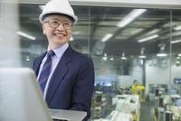 Smiling manager using laptop in factory 11096016190| 写真素材・ストックフォト・画像・イラスト素材|アマナイメージズ
