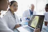 Doctors viewing x-ray on laptop in meeting