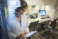 Doctor using digital tablet at nurses station
