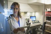 Pensive doctor using digital tablet at nurses station