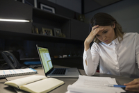 Stressed businesswoman working late in office