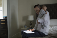 Father using digital tablet holding baby son bed