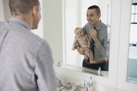 Father getting dressed feeding baby son with bottle