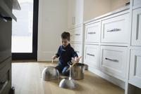 Boy banging on pots on kitchen floor 11096016762| 写真素材・ストックフォト・画像・イラスト素材|アマナイメージズ