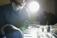 Plastic surgeon selecting surgical scissors in operating room