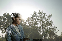 Digital composite businesswoman working on laptop against trees
