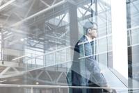 Digital composite businessman looking through modern window