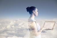 Digital composite businesswoman using laptop in clouds