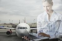 Digital composite businesswoman using laptop against airplane tarmac