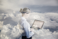 Digital composite businesswoman using laptop in clouds
