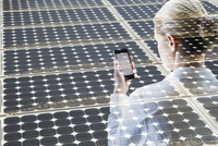 Digital composite businesswoman using cell phone solar panels