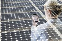Digital composite businesswoman using cell phone solar panels 11096017076| 写真素材・ストックフォト・画像・イラスト素材|アマナイメージズ