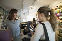 Yarn store owner shopper paying credit card machine