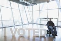 Portrait man wheelchair next to I Voted text