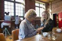 Daughter showing mother engagement ring in coffee shop