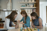 Girls decorating cupcakes with frosting in kitchen