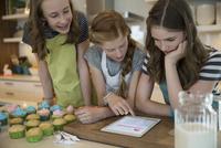 Girls reading recipe digital tablet baking cupcakes kitchen