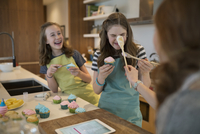 Playful girls frosting cupcakes in kitchen