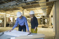Architect and engineer reviewing blueprints office construction site