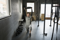 Man doing lunges gym with weight plate overhead
