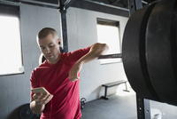 Man texting with cell phone at barbell rack
