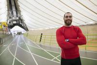 Portrait confident male runner on indoor track