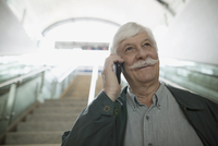 Smiling senior man mustache talking on cell phone