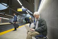 Senior man using laptop on subway station platform