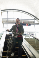 Businessman with bicycle descending escalator at train station