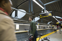 Businessman with bicycle on subway station platform
