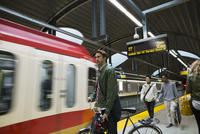 Businessman with bicycle watching arriving subway on platform