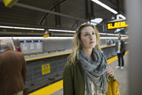 Woman looking up information board subway station platform