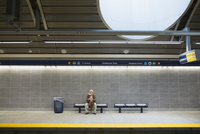 Senior man waiting on bench subway station platform