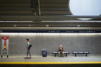 Senior man watching man skateboard subway station platform