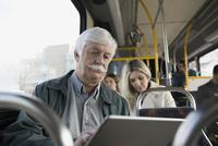 Senior man using digital tablet on bus