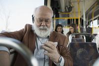Senior man listening music with headphones on bus