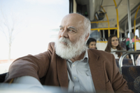 Pensive senior man riding bus looking out window