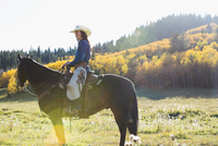 Woman sitting horseback in sunny autumnal field