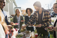 Neighbors enjoying potluck in sunny front yard