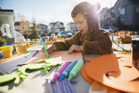 Boy in Halloween costume doing crafts front yard