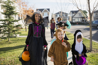 Kids in Halloween costumes on neighborhood sidewalk