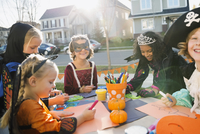 Kids in Halloween costumes doing crafts front yard