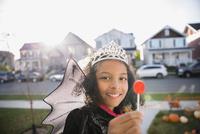 Portrait smiling girl Halloween princess costume enjoying lollipop