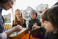 Woman candy greeting trick or treaters front stoop