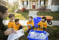 Coach and boys sports team gathering recycling neighborhood