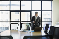 Businessman texting with cell phone in conference room