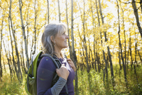 Woman with backpack hiking in autumn woods